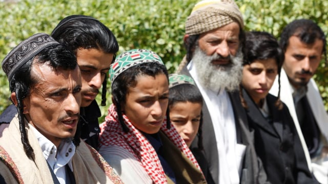 Mehrere jemenitische Juden sitzen auf einer Bank
