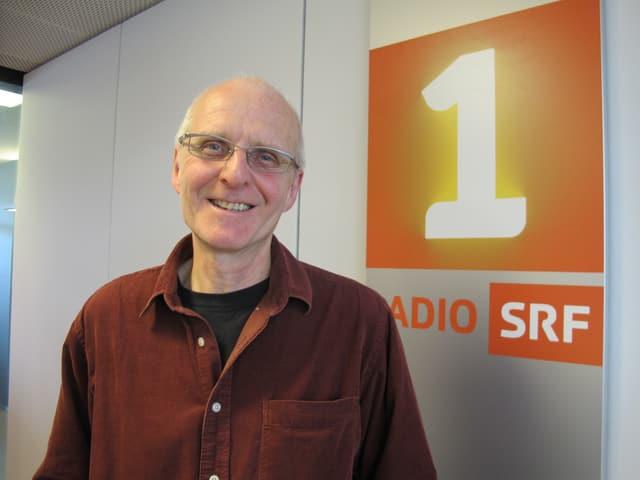 Porträt von Jürg Stauffer vor dem SRF1 Logo.