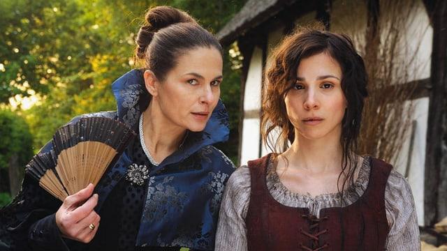 Zwei Frauen stehen neben einem Haus im Freien nebeneinander.