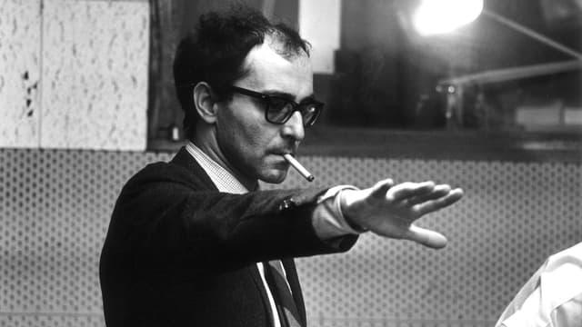 Ein Mann im Anzug mit Zigarette im Mund streckt den Arm nach vorne.