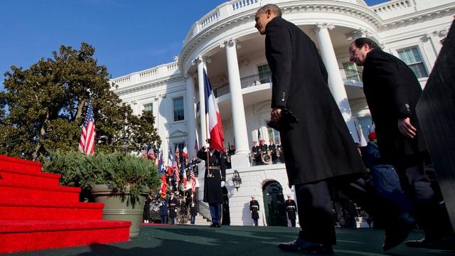 Die Präsidenten Obama und Hollande schreiten vor dem Weissen Haus auf ein rotes Podest zu.