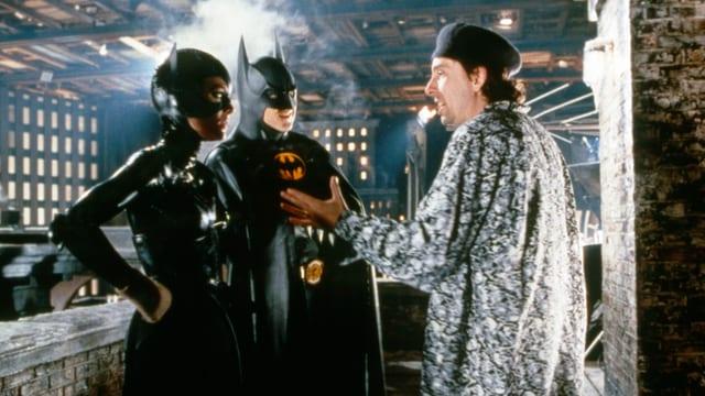 Auf dem Bild sind der Regisseur Tim Burton und die Schauspieler Michelle Pfeiffer und Michael Kaeton in ihren Kostümen zu sehen.
