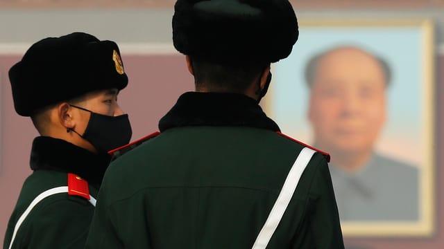 Polizisten mit Mundschutz vor einem Mao-Bild.