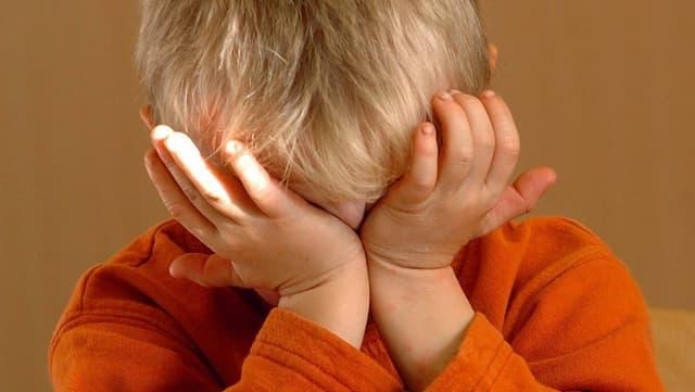 Ein Kind presst seine Hände gegen sein Gesicht