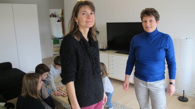 Zwei Frauen blicken in die Kamera, im Hintergrund Kinder und eine Frau am spielen.
