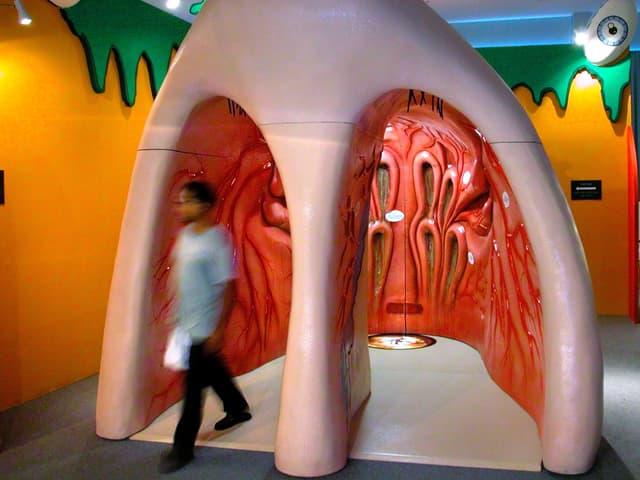 Ein Mann verlässt gerade die rechte Nasenhöhle einer riesigen Plastiknase.