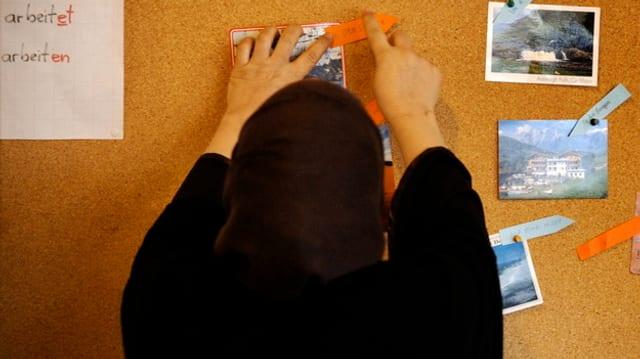 Eine Frau mit Kopftuch an einer Wandtafel