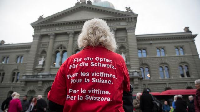 Eine Frau mit weissen Haaren von hinten, auf ihrem roten T-Shirt steht «Für die Opfer, für die Schweiz».