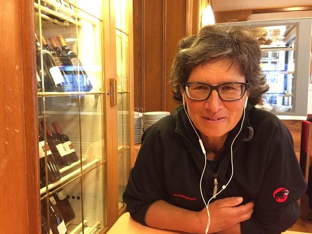 Marlies Longatti sitzt an einem Tisch und hat Kopfhörer in den Ohren.