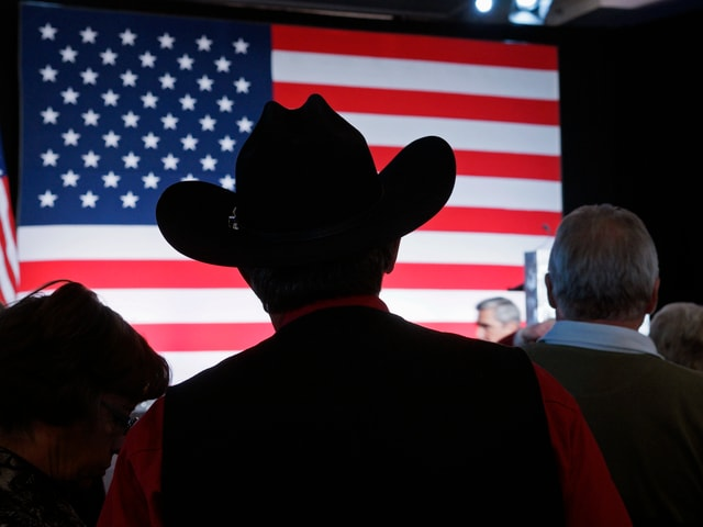 Mann mit Cowboyhut vor einer USA-Flagge