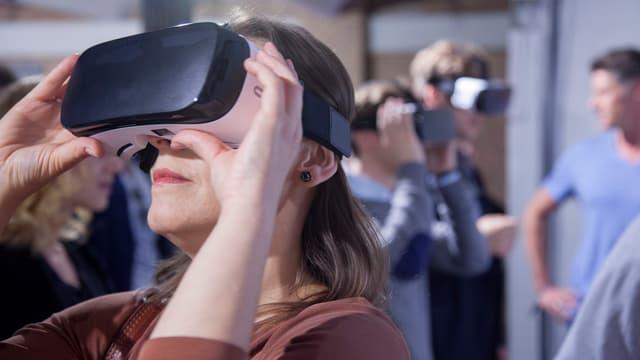 Eine Frau schaut in eine VR-Brille.