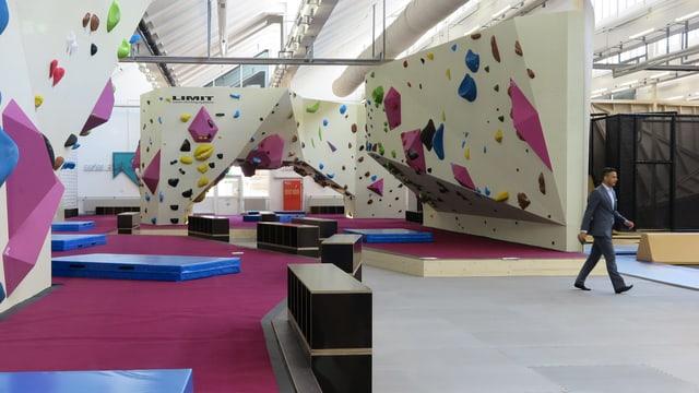 Eine Halle mit Kletterwänden und Matten auf dem Boden.