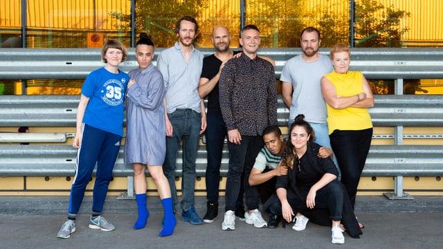 Neun Personen posieren für ein Foto vor einem Haus