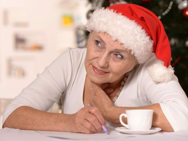 Eine Seniorin mit Chlausenmütze schreibt etwas auf und trinkt Kaffee.