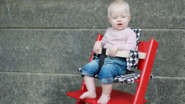 Kind auf rotem Kinderstuhl