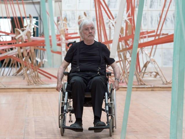 Der Künstler im Rollstuhl inmitten seiner Skulpturen in der Ausstellung.