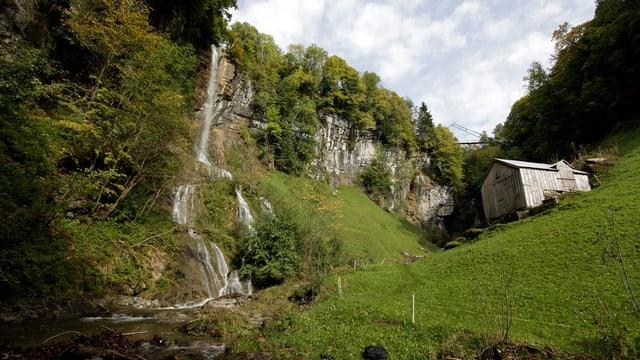 Fallenbach, Wasserfall, daneben Wiesen und eine kleine Hütte.