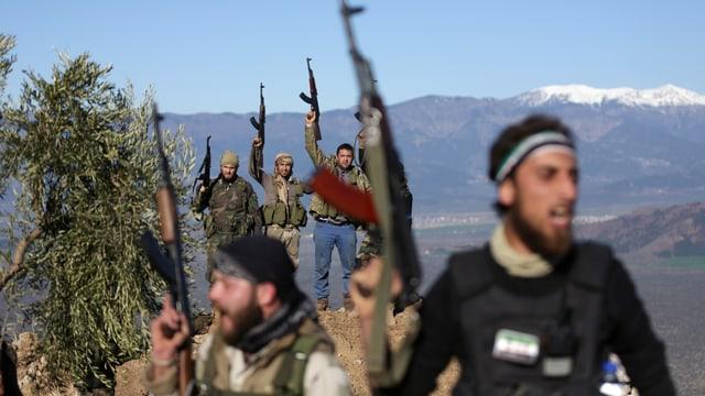Männer stehen auf Hügeln und halten ihre Sturmgewehre in die Höhe.