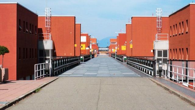 Ein Weg, der zwischen zweistöckigen, orangen Häusern hindurch führt.