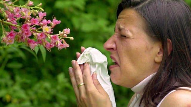 Purtret d'ina dunna che stat davant ina flur e sturnidescha en in faziel da nas.