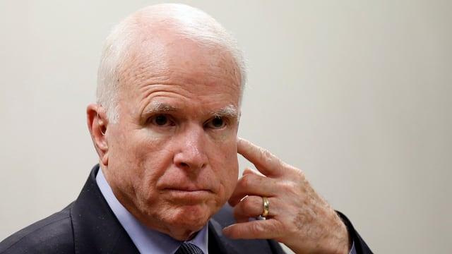 John McCaine hält sich die linke Hand an die Wange.