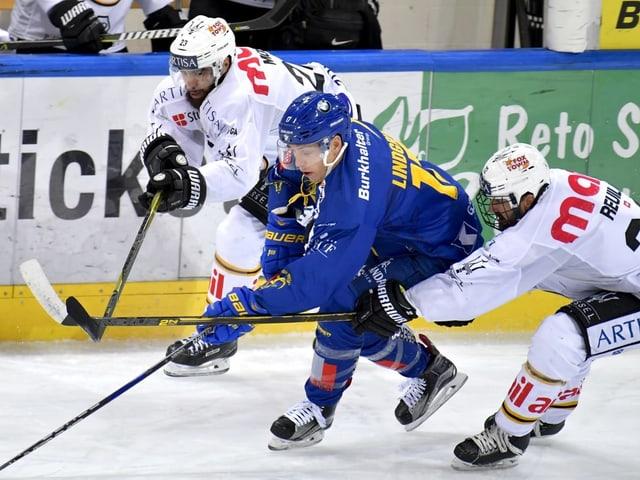 Dus hockeyans da Lugano Giovanni Morini (san.) e Sebastien Reuille (dretg) prendan en la zanga Perttu Lindgren dal HCD.
