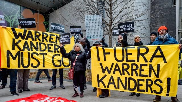 Leute protestieren vor dem Whitney Museum in New York: sie halten gelb-schwarze Transparente.