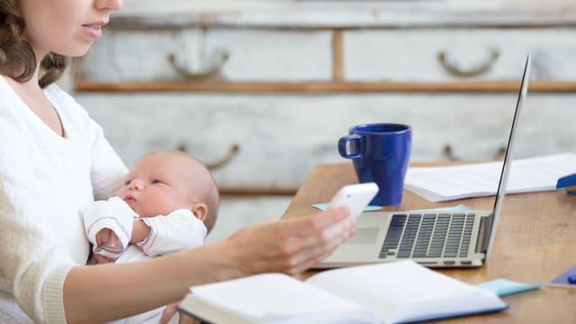 Eine Mutter hält ihr Kind in den Armen und hat den Laptop vor sich auf dem Tisch.
