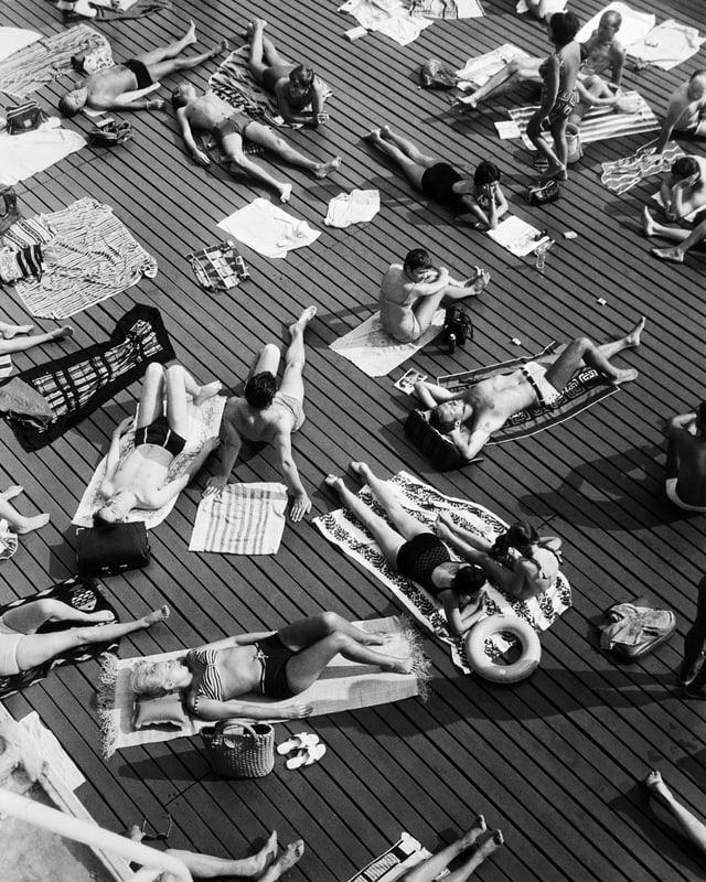 Menschen in Badeanzügen liegen auf einem Holzrost