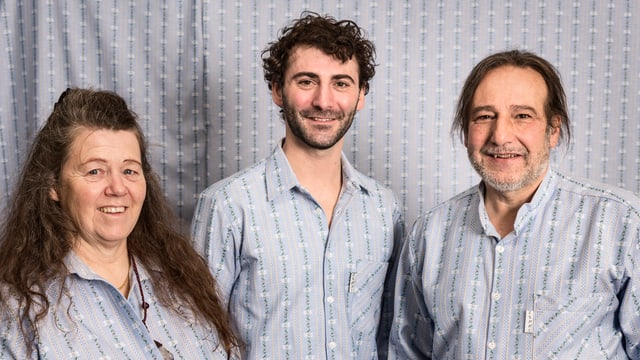 Zwei ältere Personen und eine jüngere schauen in die Kamera: Alle drei tragen die gleiche Bluse.