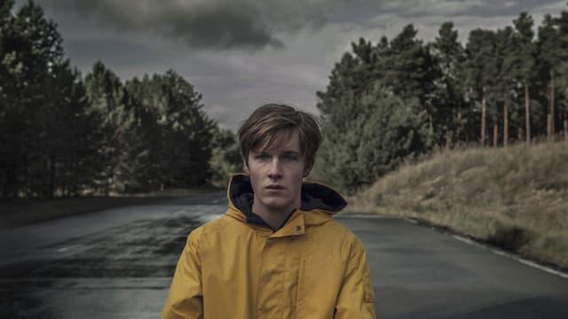 Ein junger Mann mit gelber Regenjacke steht auf einer breiten Strasse, im Hintergrund ein Wald.