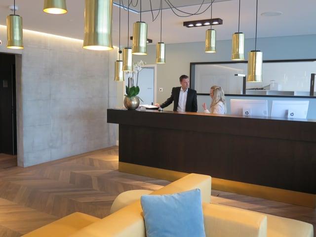Rezeption im Hotel: Direktor spricht mit Angestellter