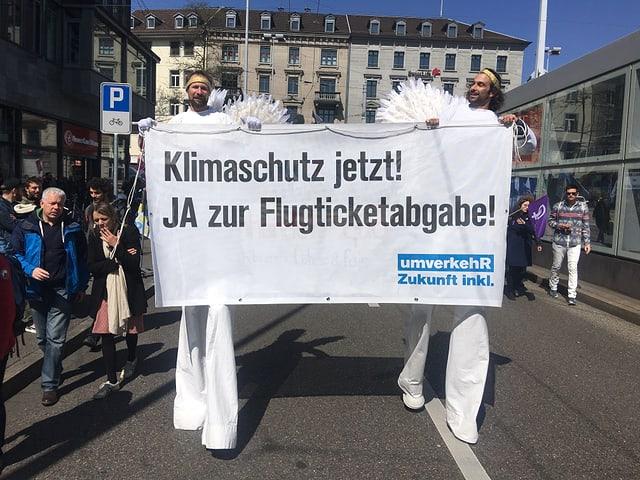 Zwei weissgekleidete Männer auf Stelzen halten ein Flugblatt mit der Aufschrift: «Klimaschutz jetzt! JA zur Flugticketabgabe.»