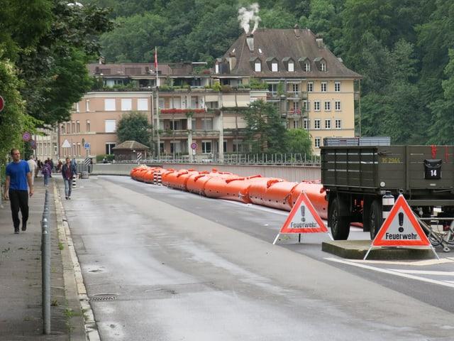 Passanten laufen auf einer Strasse, welche rechts durch rote Schläuche geschützt ist.