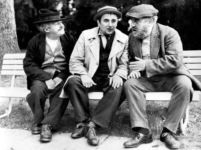 Drei Männer sitzen auf einer Bank und sprechen miteinander.