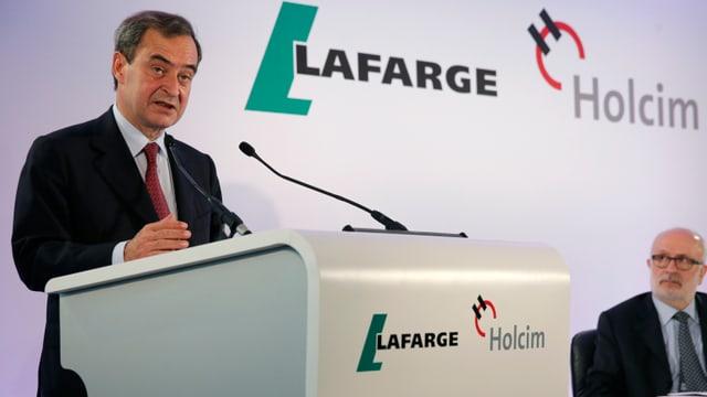 Bruno Lafont discurra en in microfon, davos el ils logos da Lafrage e Holcim