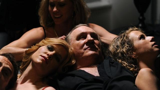 Ein Mann liegt auf dem Rücken, umgeben von vier leicht bekleideten Frauen.