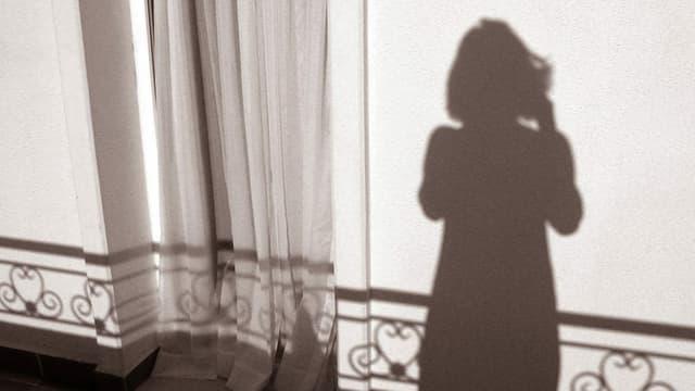 Schatten im Sonnen Gegenlicht einer Frau auf einem Balkon