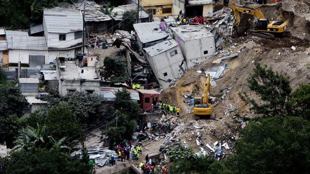 Bagger an zerstörten Häusern