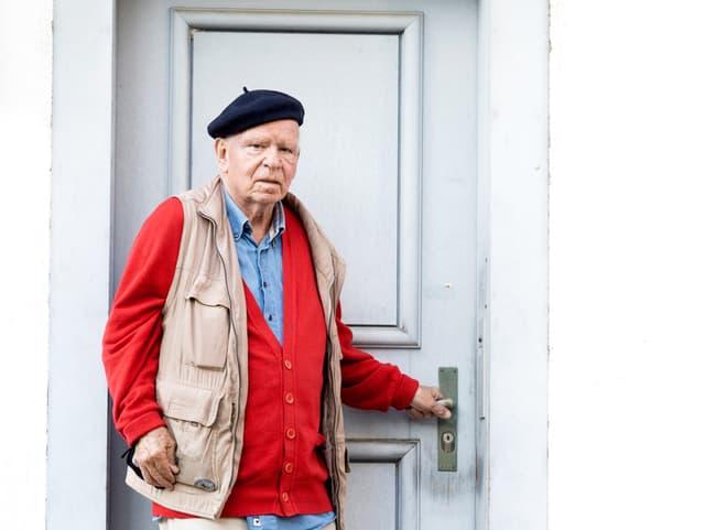Ein Mann mit Béret steht vor einer Haustüre, die Hand an der Türklinke.