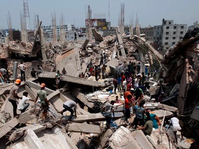 Männer klettern über zerbrochene Beton-Bauelemente des zusammengestürzten Gebäudes.
