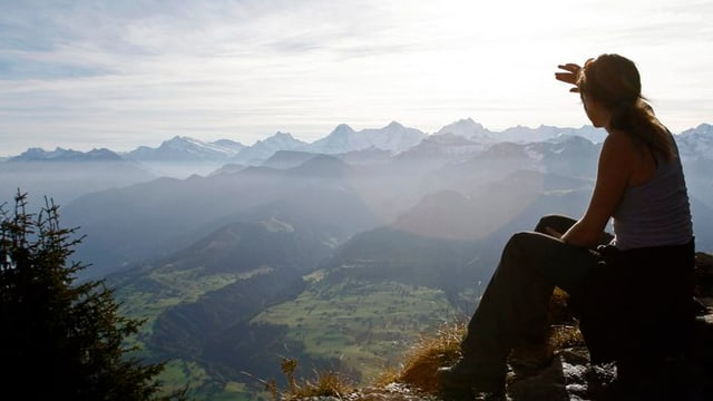 Frau sitzt auf Berggipfel und guckt in die Ferne.