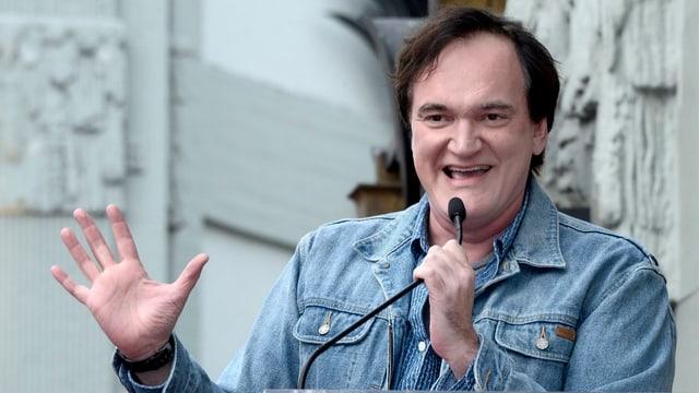 Quentin Tarantino vor einer Statue. Er spricht ins Mikrofon und hebt seine rechte Hand.