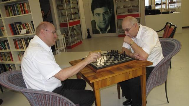 Roland und Werner Rupp sitzen an einem Tisch und spielen Schach.