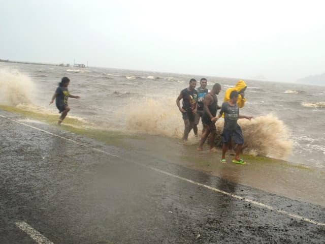 Menschen gehen am Rande einer Strasse, als grosse Wellen ans Ufer preschen