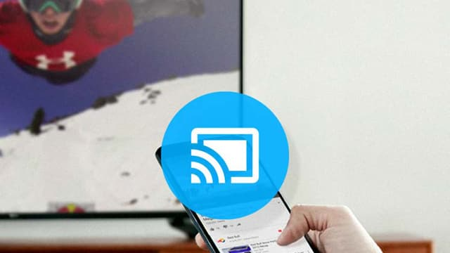 Eine Hand hält ein Smartphone, im Hintergrund ist ein Fernseher zu sehen, über das Bild ist das «Cast»-Symbol des Google Chromecasts zu sehen.