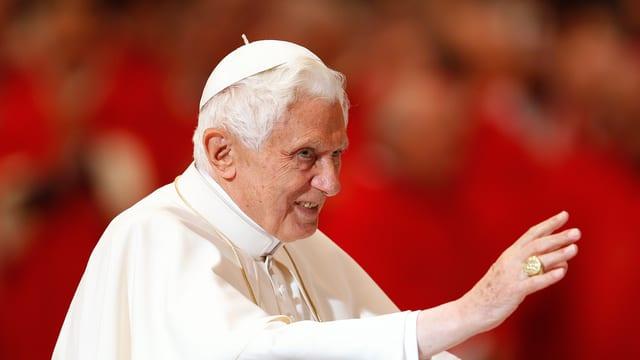 Nahaufnahme des Papstes, der die rechte Hand grüssend ausstreckt und aus dem rechten Bildrand schaut.