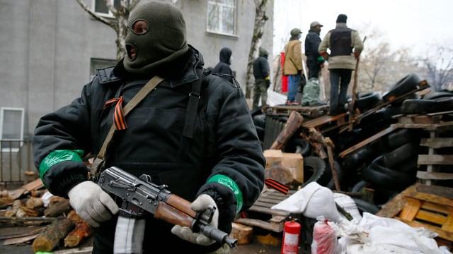 Vermummter Separatist mit einer Schnellfeuerwaffe steht vor einer Barrikade.