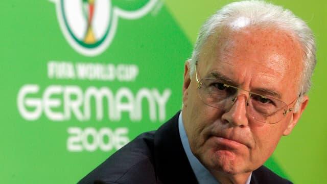 Frans Beckenbauer vor dem Logo der WM 2006