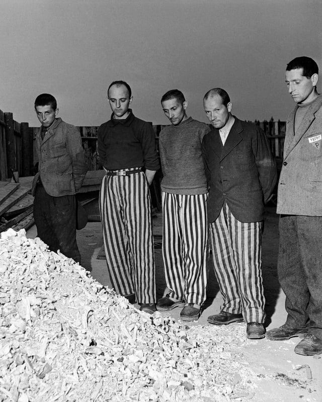 KZ-Überlebende hinter einem Steinhaufen.